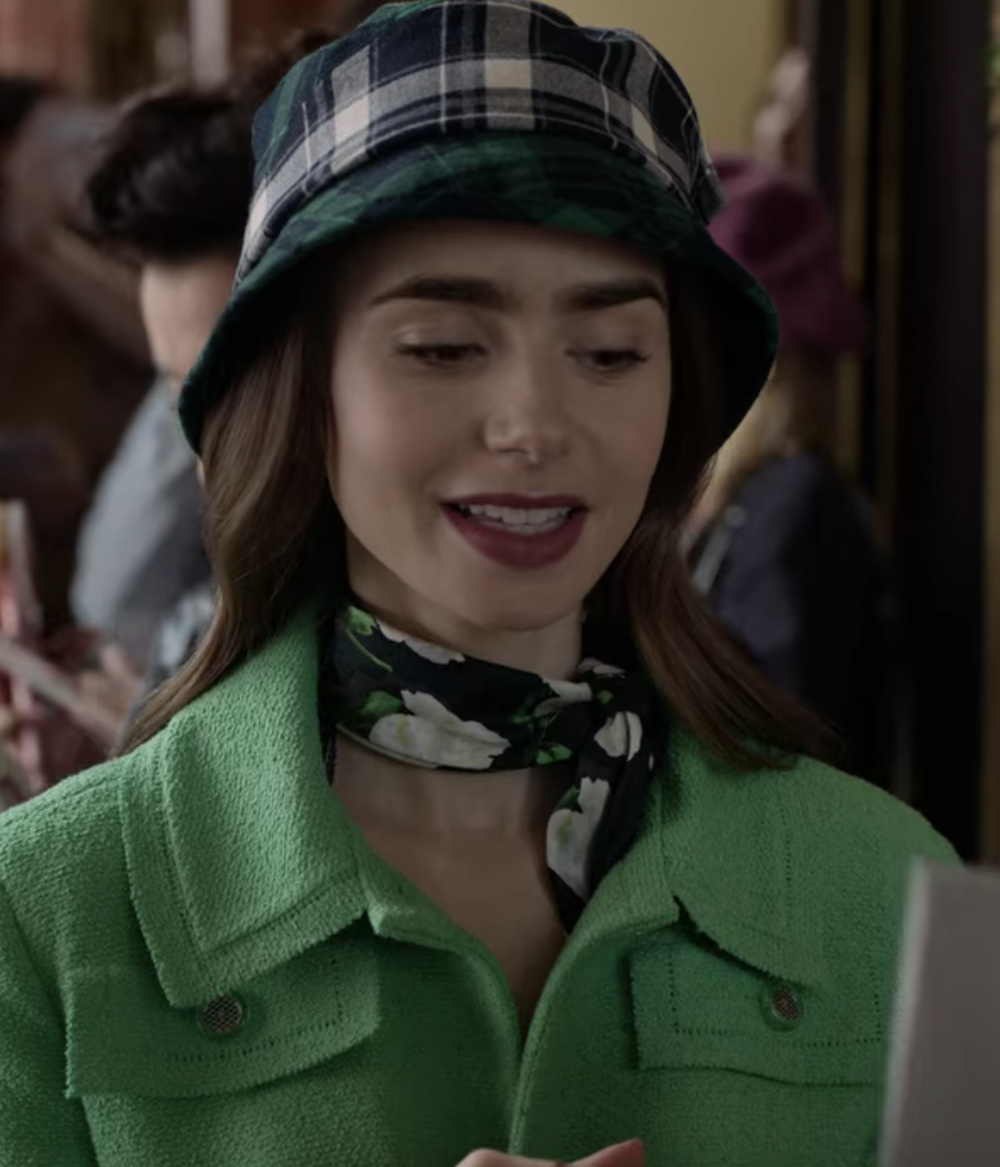 Emily looks downwards while wearing a green plaid bucket hat, a black neckerchief with white flowers, and a green coat