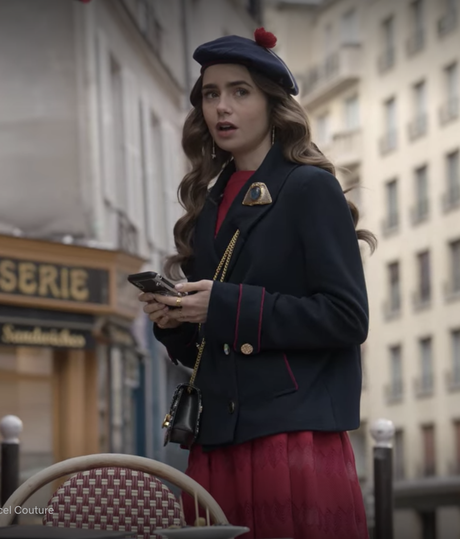 Emily looks up from her phone, shook, wearing a red high necked dress, navy blazer with an oversized brooch on the lapel, and a navy beret with a red poof on the top