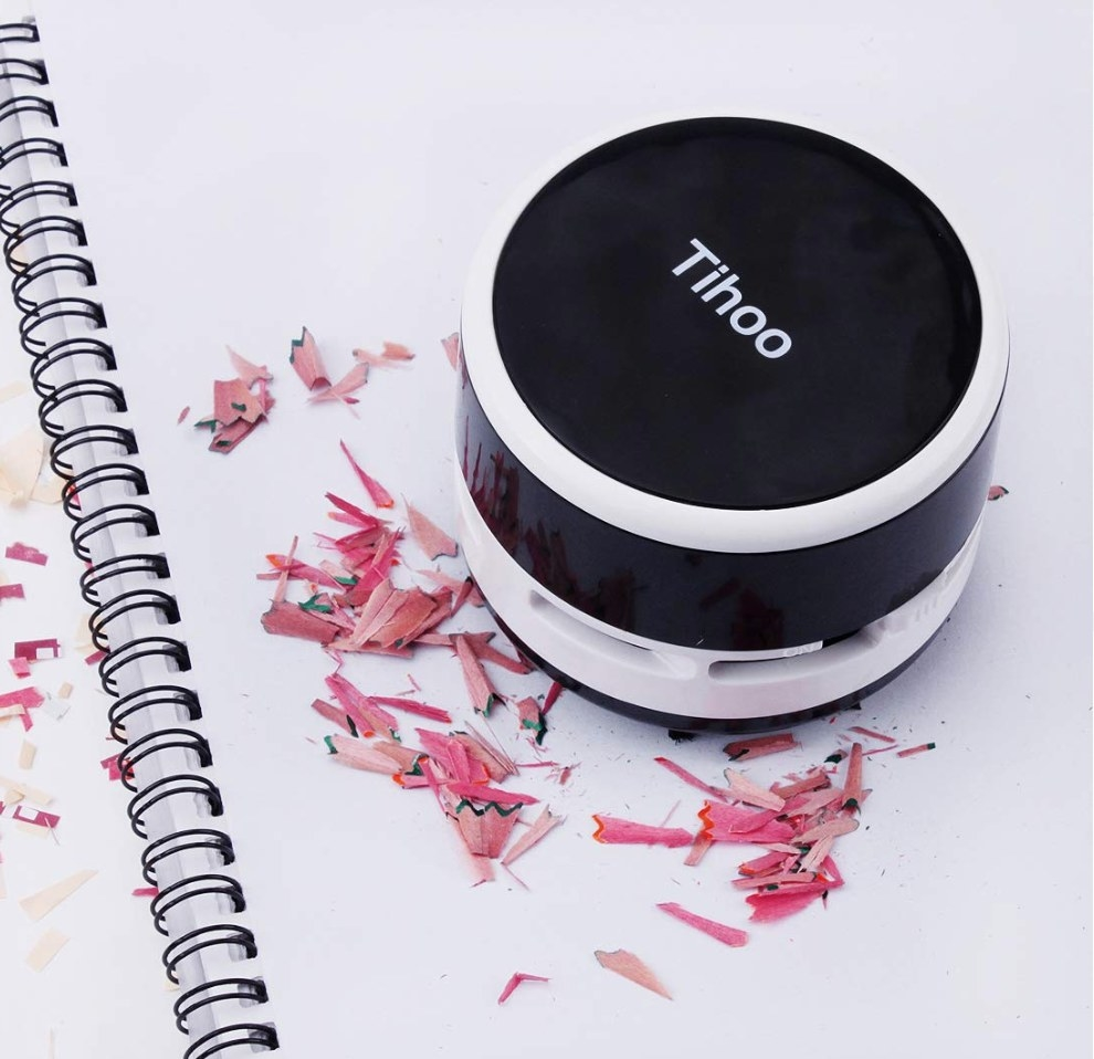 Small black and white round handheld vacuum with Tihoo logo in white, cleaning up pencil shavings