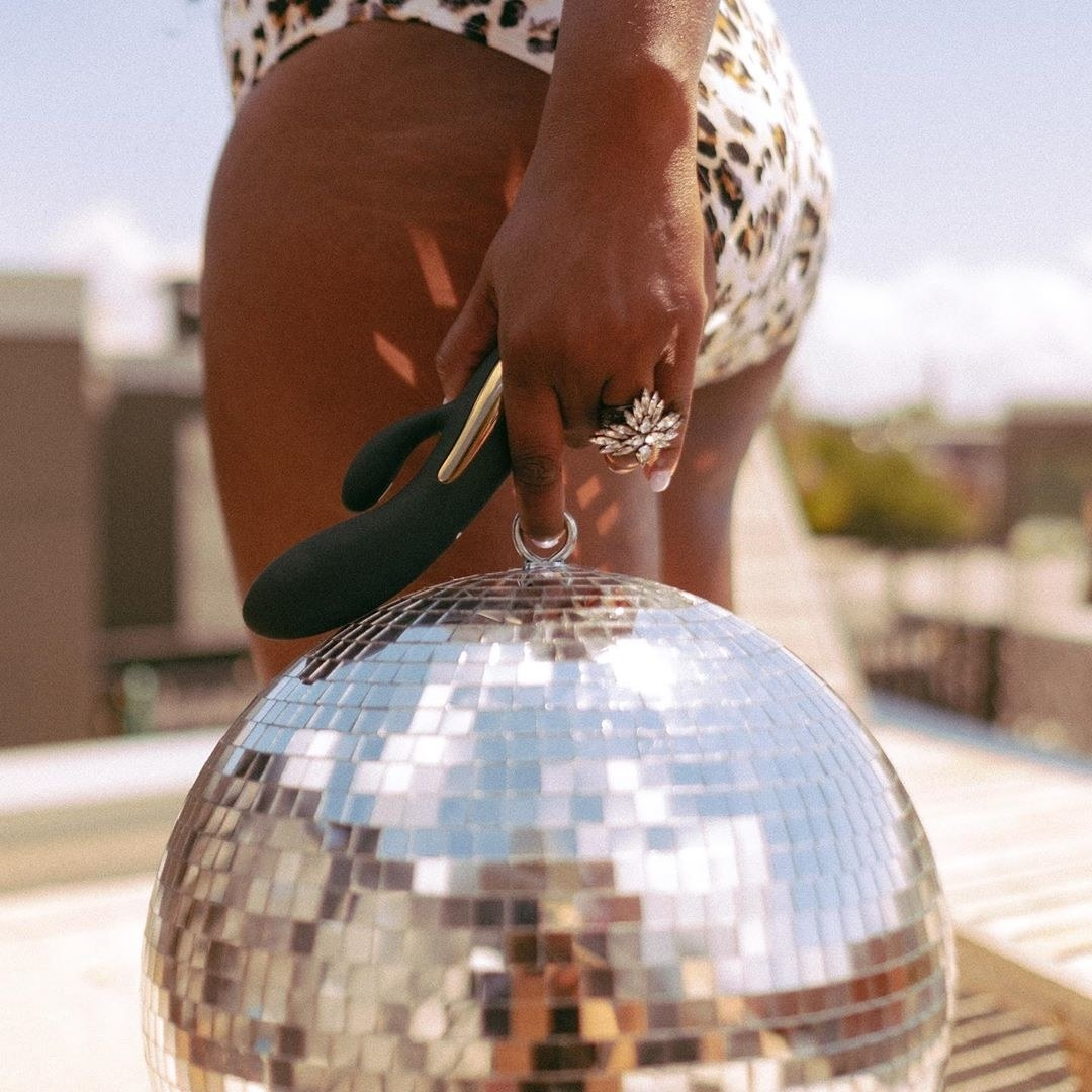 A model holds the Diosa Vibrator in the same hand as a disco ball