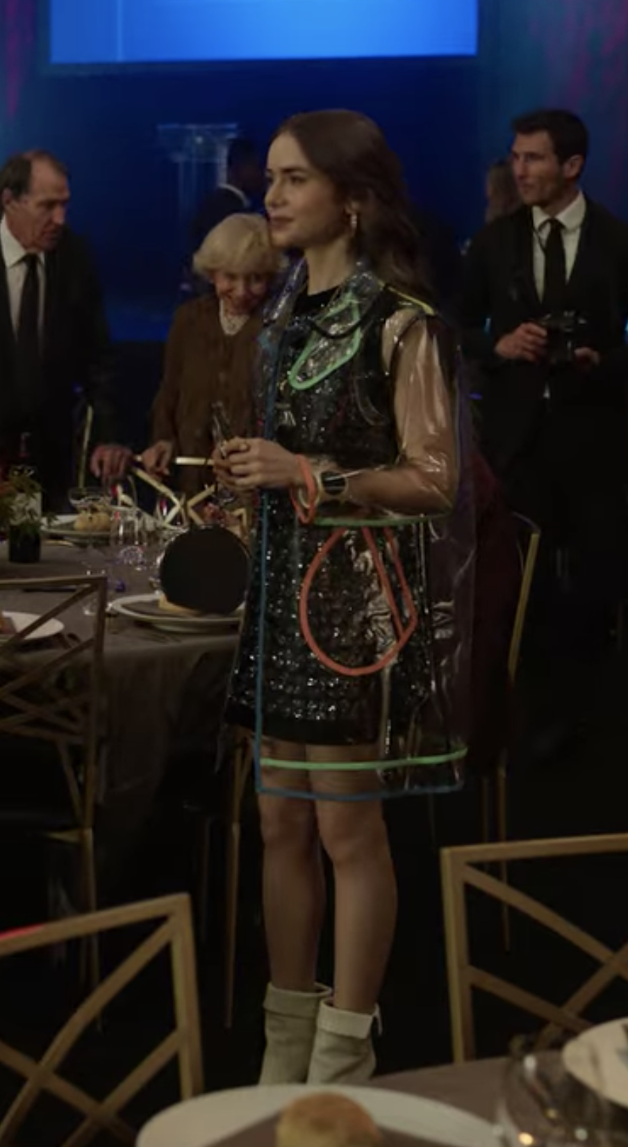 Emily is turned to the side wearing a black and silver mini sheath dress, shite calf-length boots, and a clear plastic coat with multi-colored lines running through it