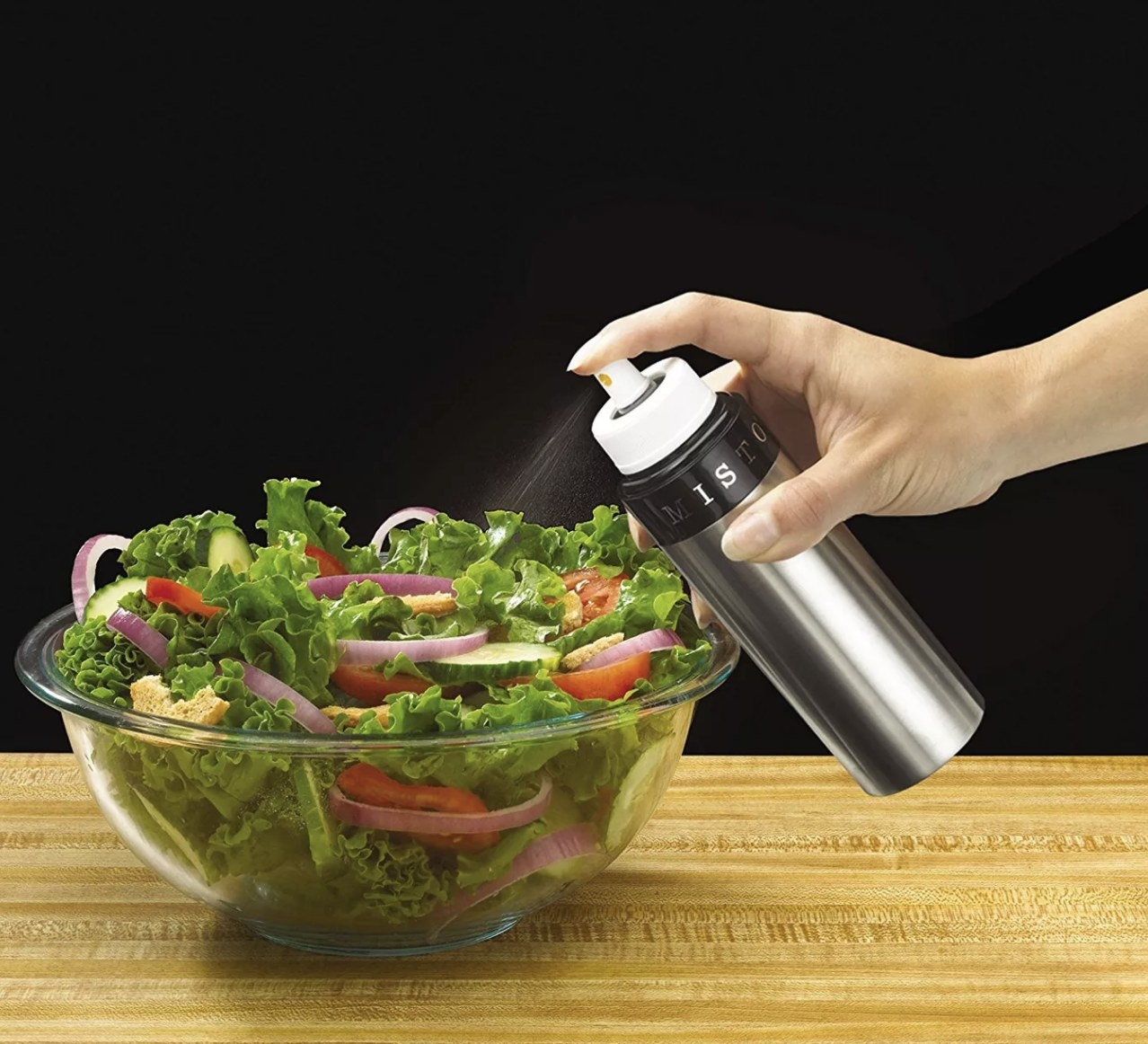 a person misting a salad with misto oil sprayer
