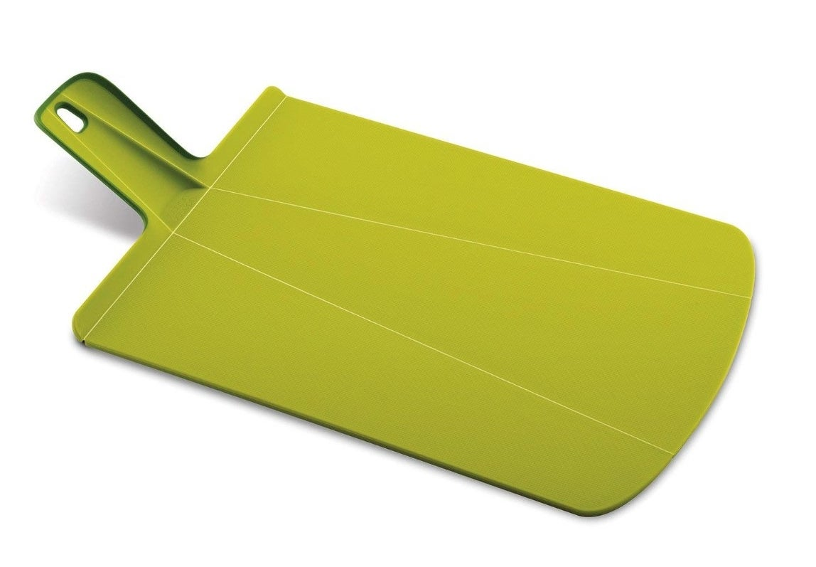 The foldable cutting board in green with handle
