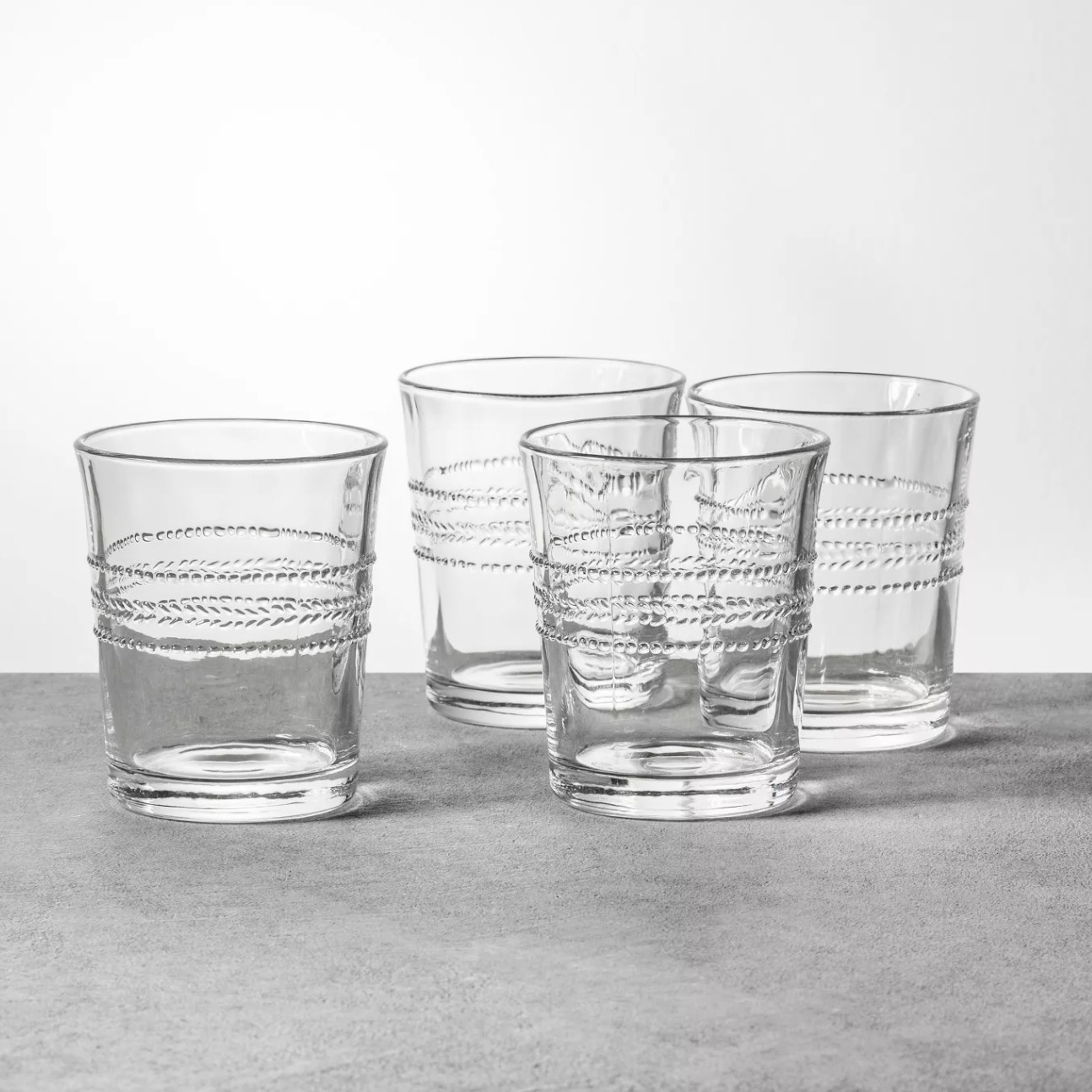 four short clear glasses with etching around the glass