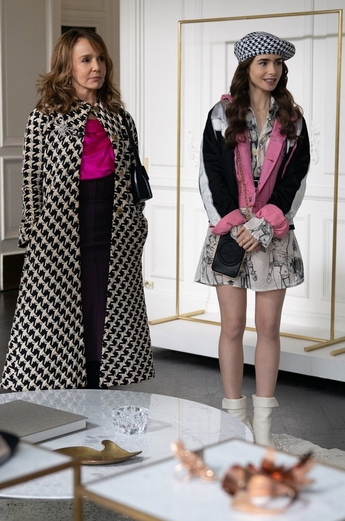 Sylvie and Emily stand in the atelier; Emily is wearing white mid-calf boots, A white dress with Roman figures on it, a pink denim jacket with a black and white windbreaker on top, and a houndstooth beret