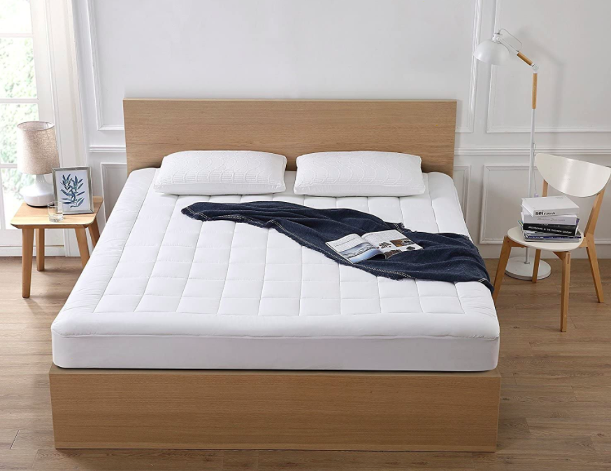 White mattress pad cover on top of white mattress on wooden bed
