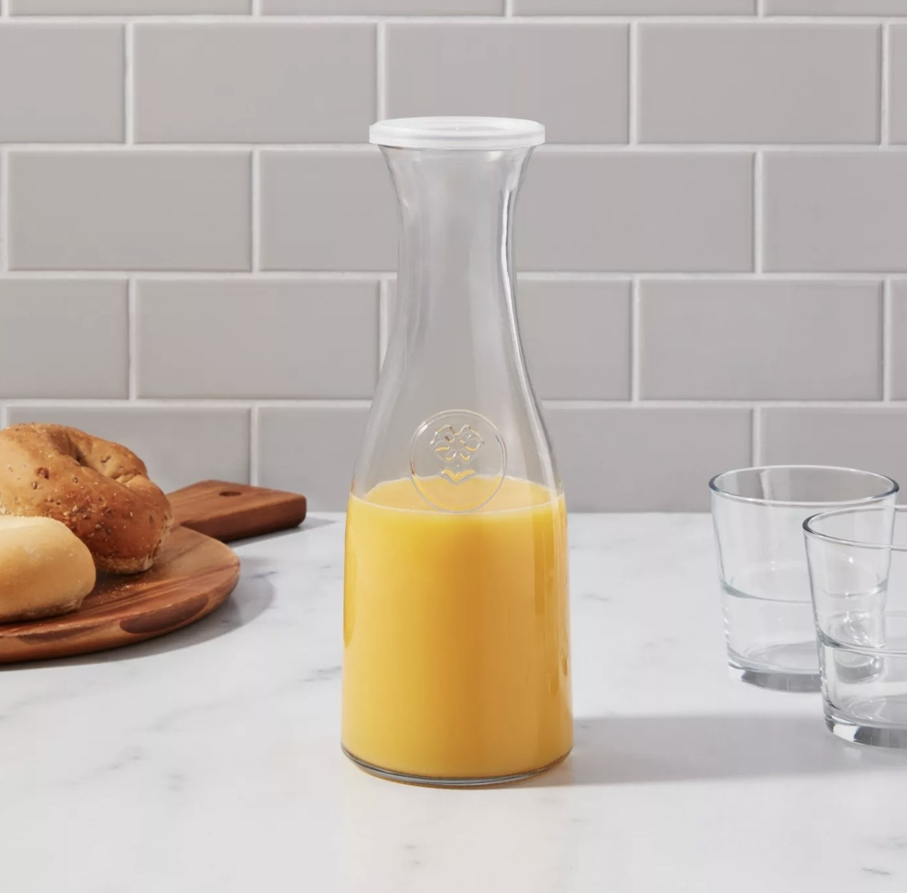 a glass carafe with a plastic lid holding orange juice
