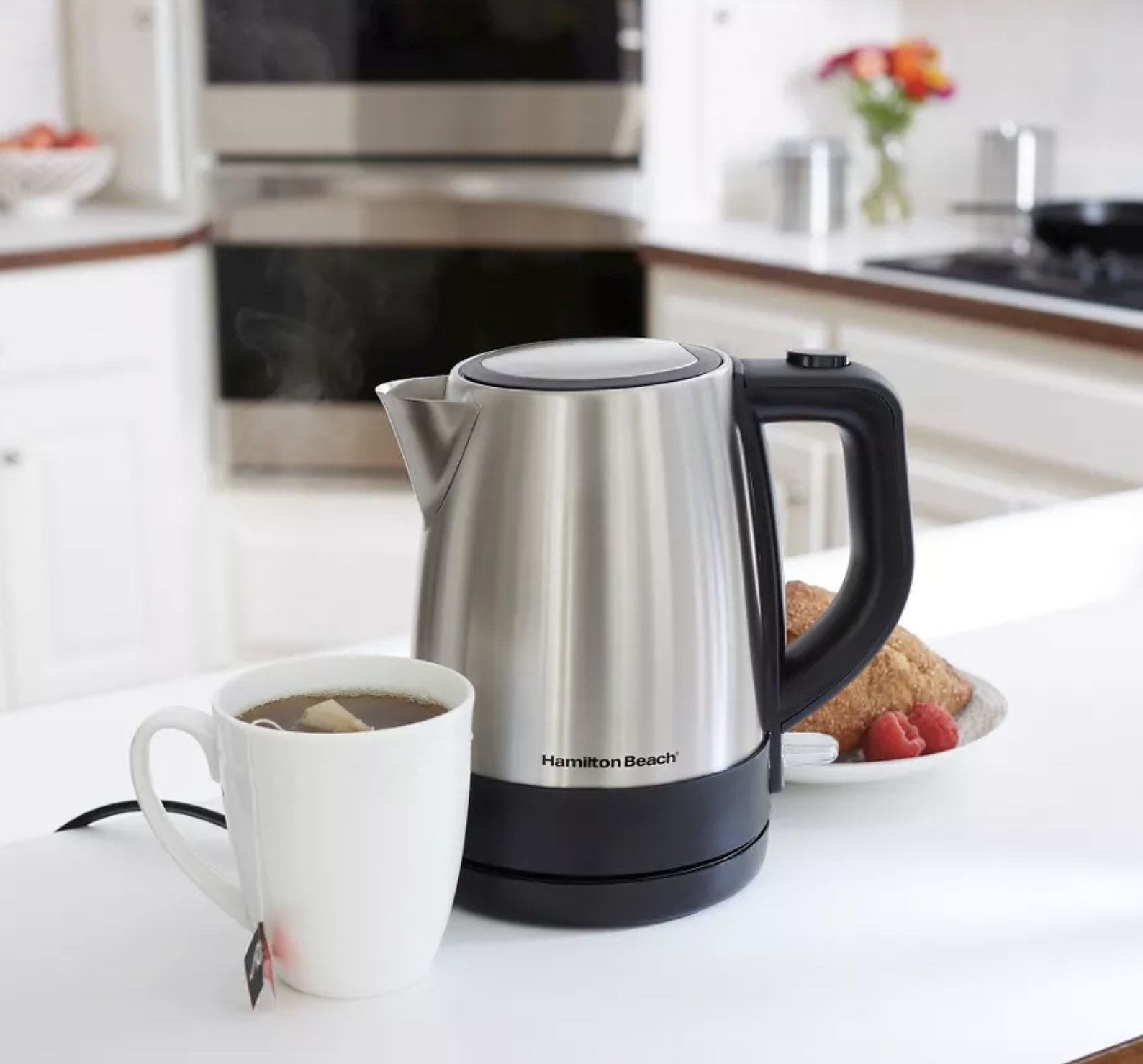 a stainless steel water kettle next to pastries and a cup of tea