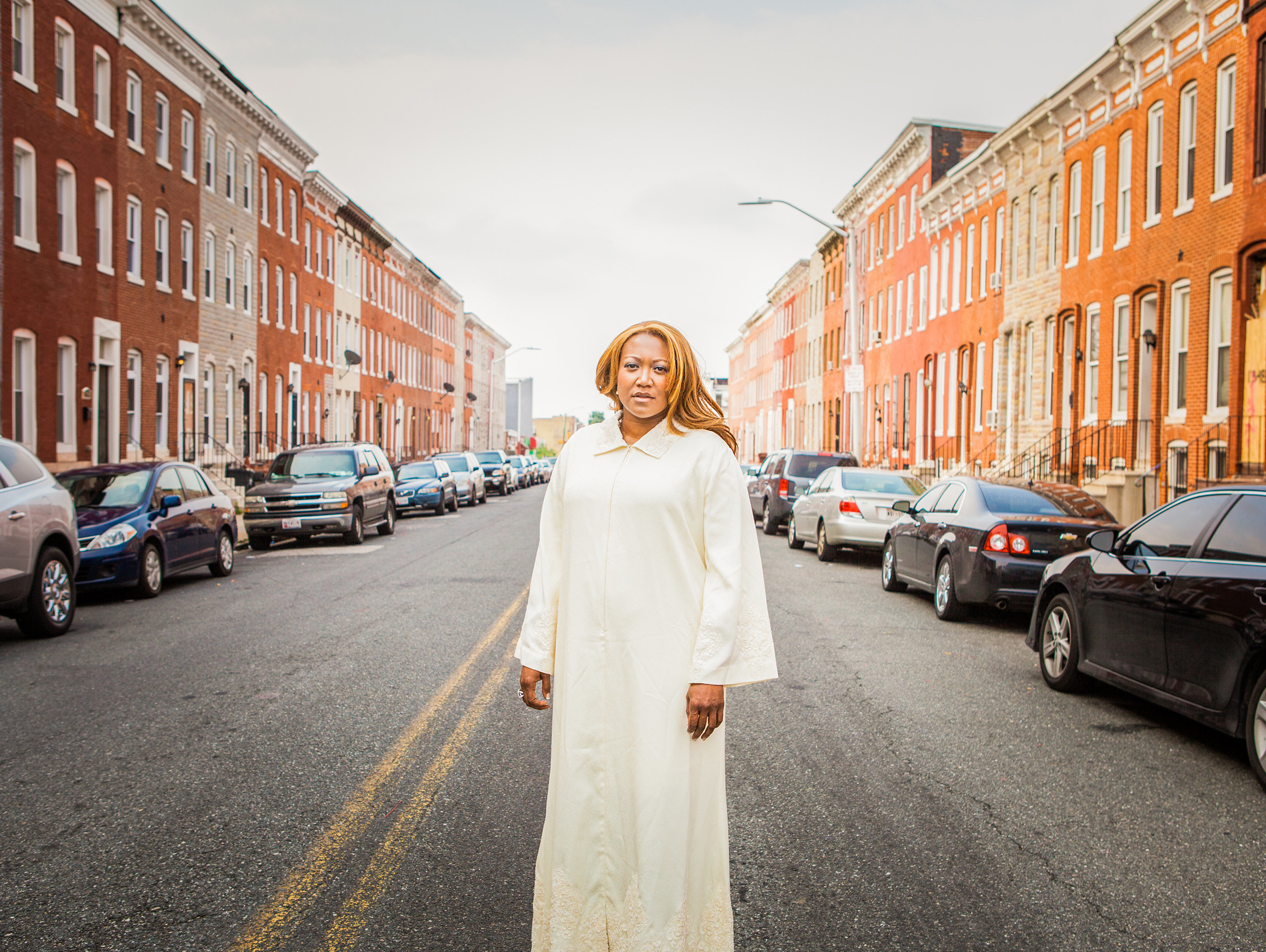 A woman in white robes on a street in Baltimore with brick row houses