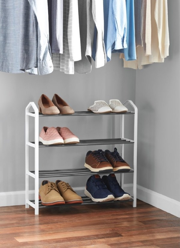 White shoe rack with six pairs of shoes on it, on wooden floor of clost