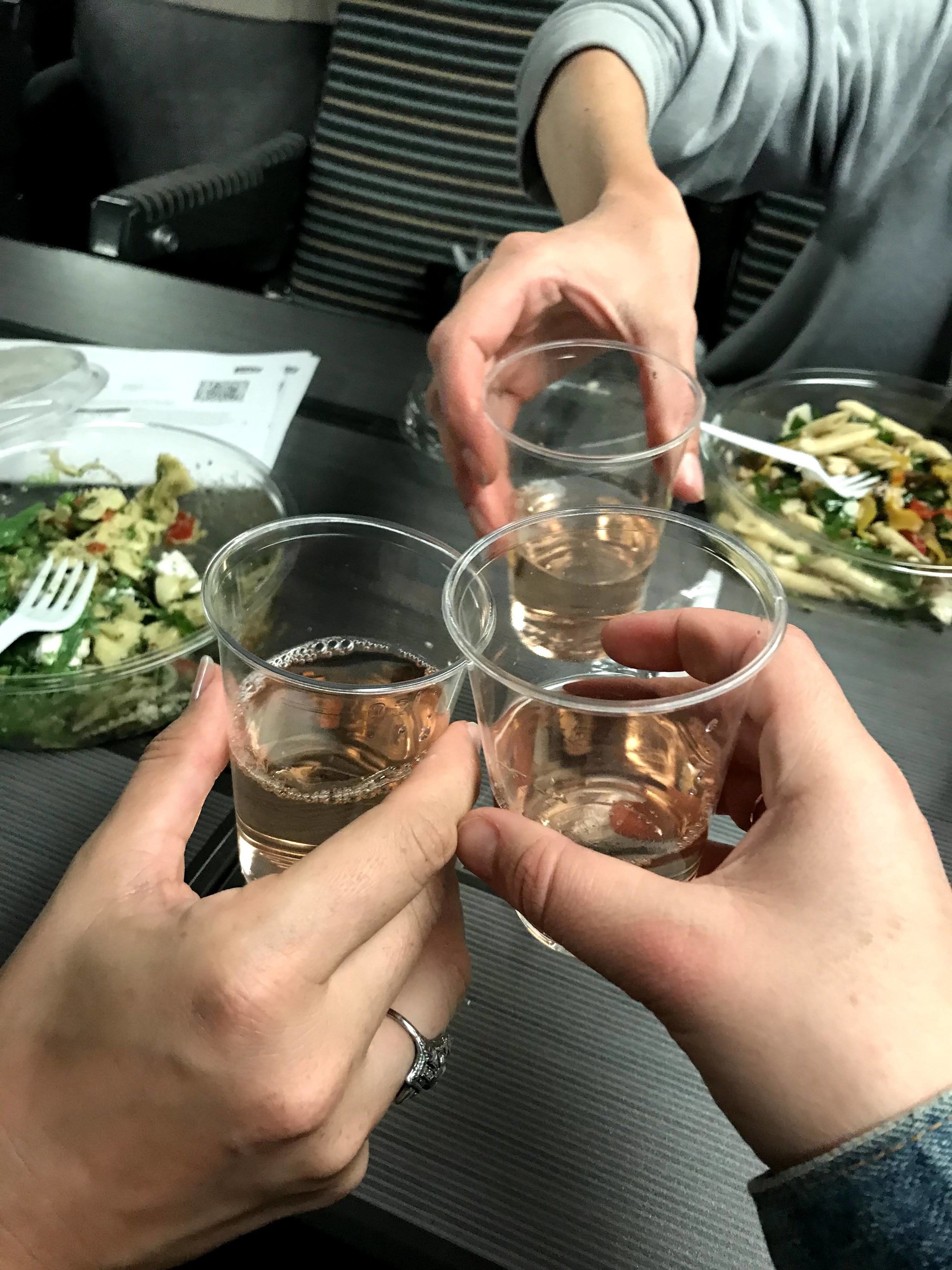 The hands of three people clinking plastic cups of wine on the train