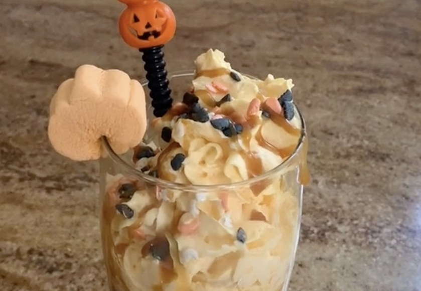 A coffee drink with lots of orange whipped cream and sprinkles