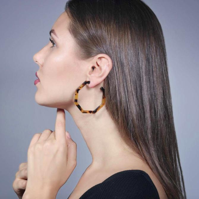 Model wears hoop tortoise-shell earrings with an off-shoulder blouse