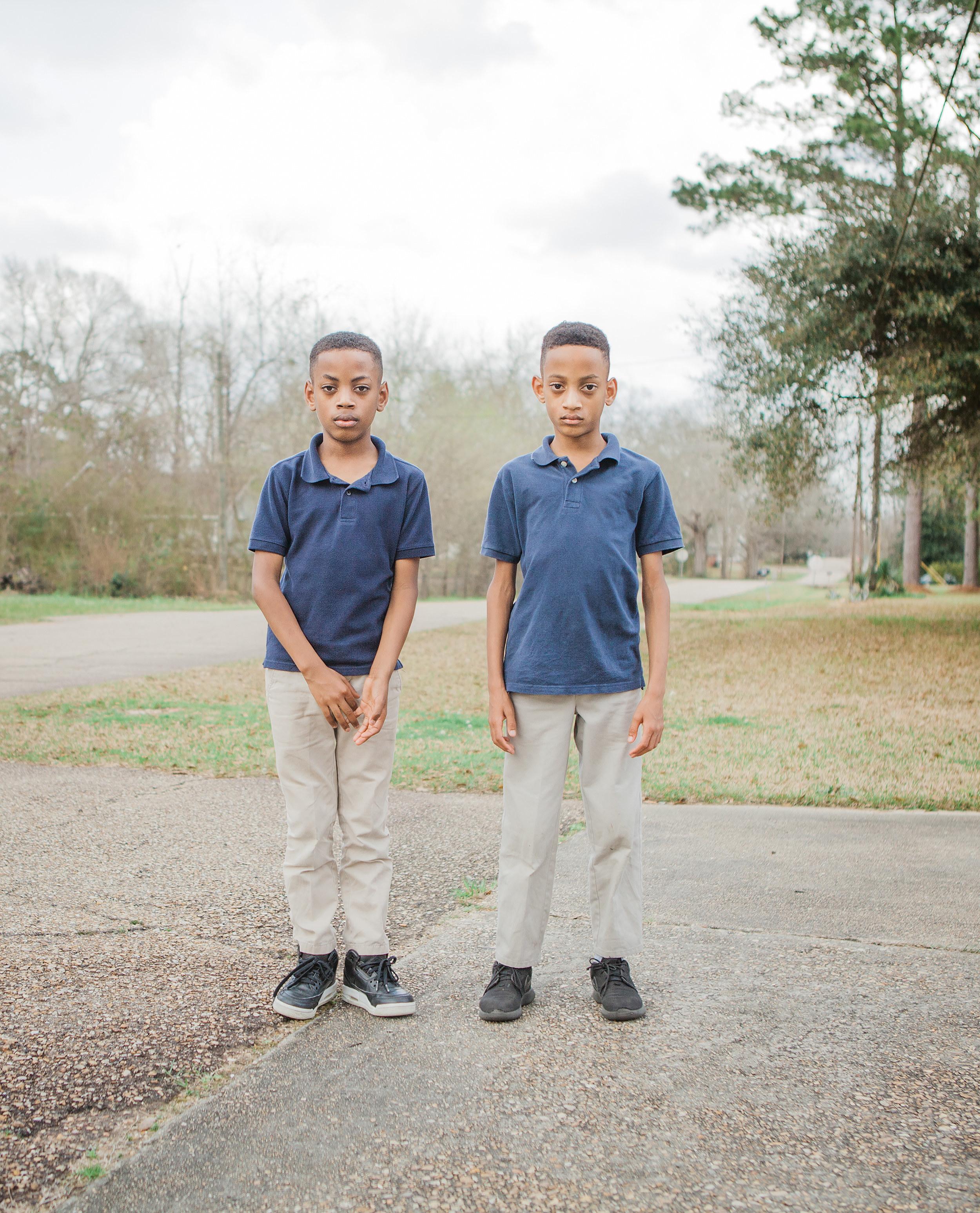 Two young boys in school uniforms on a sidewalk
