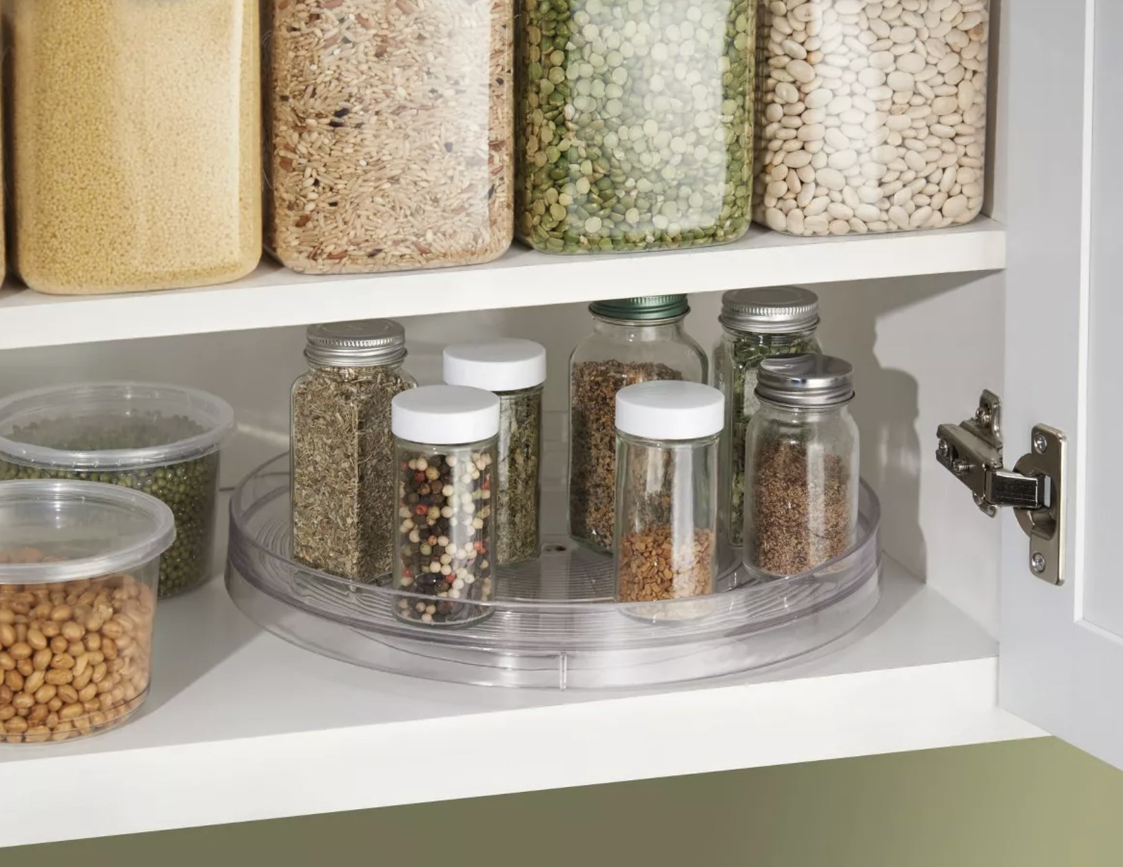 a clear lazy susan in a cupboard holding spices