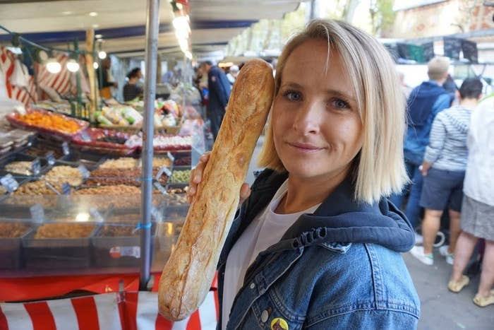 Woman holds a baguette in an outdoor market