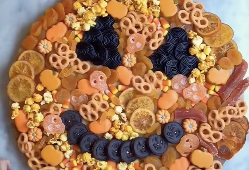 A board of food filled with cookies and pretzels that look like a pumpkin