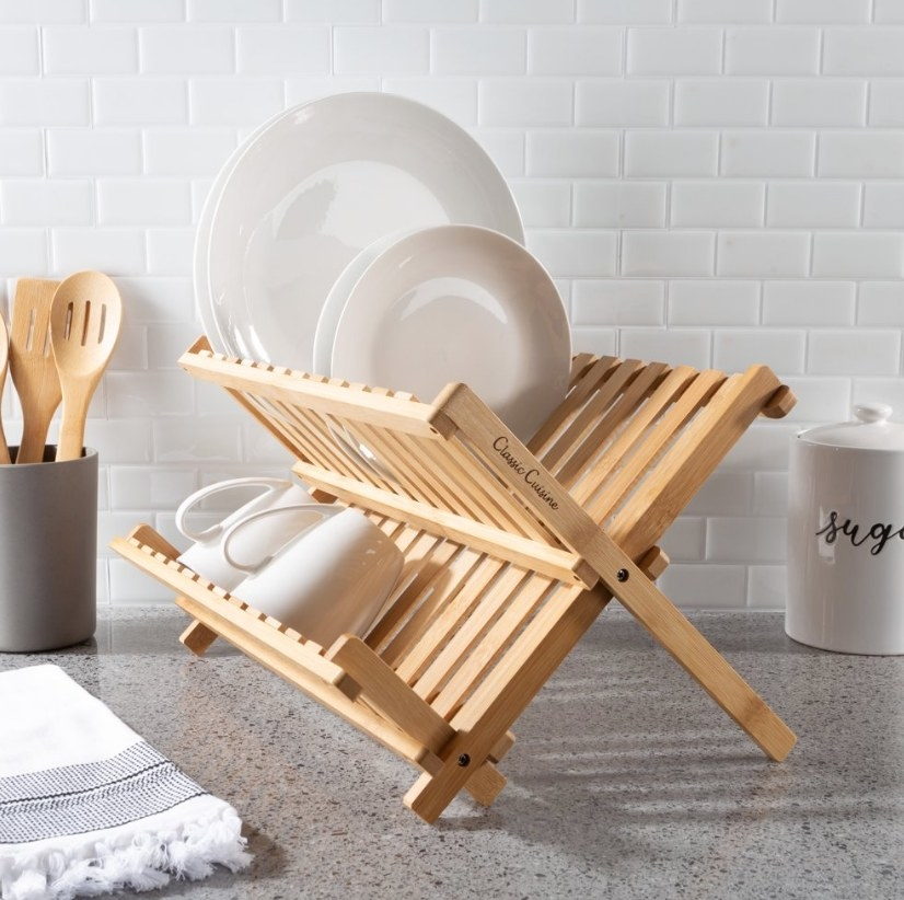Wooden dish rack with two white mugs on bottom rack and white plates on top rack