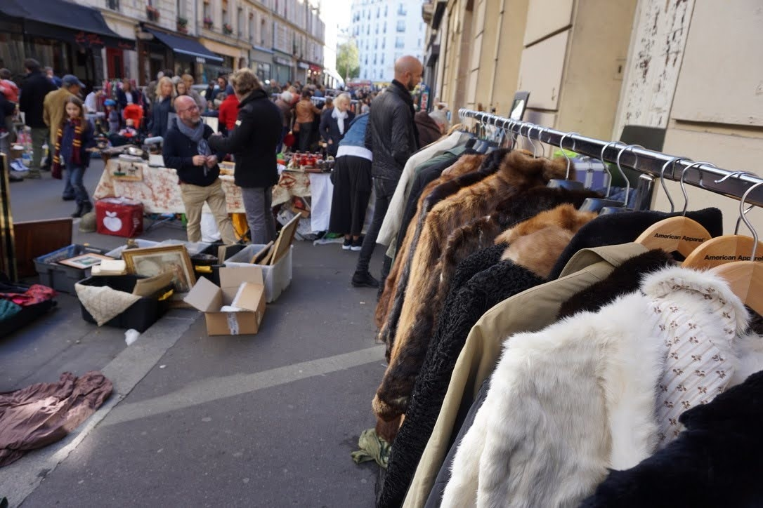 A rack of fur jackets being sold at an outdoor flea market on the street