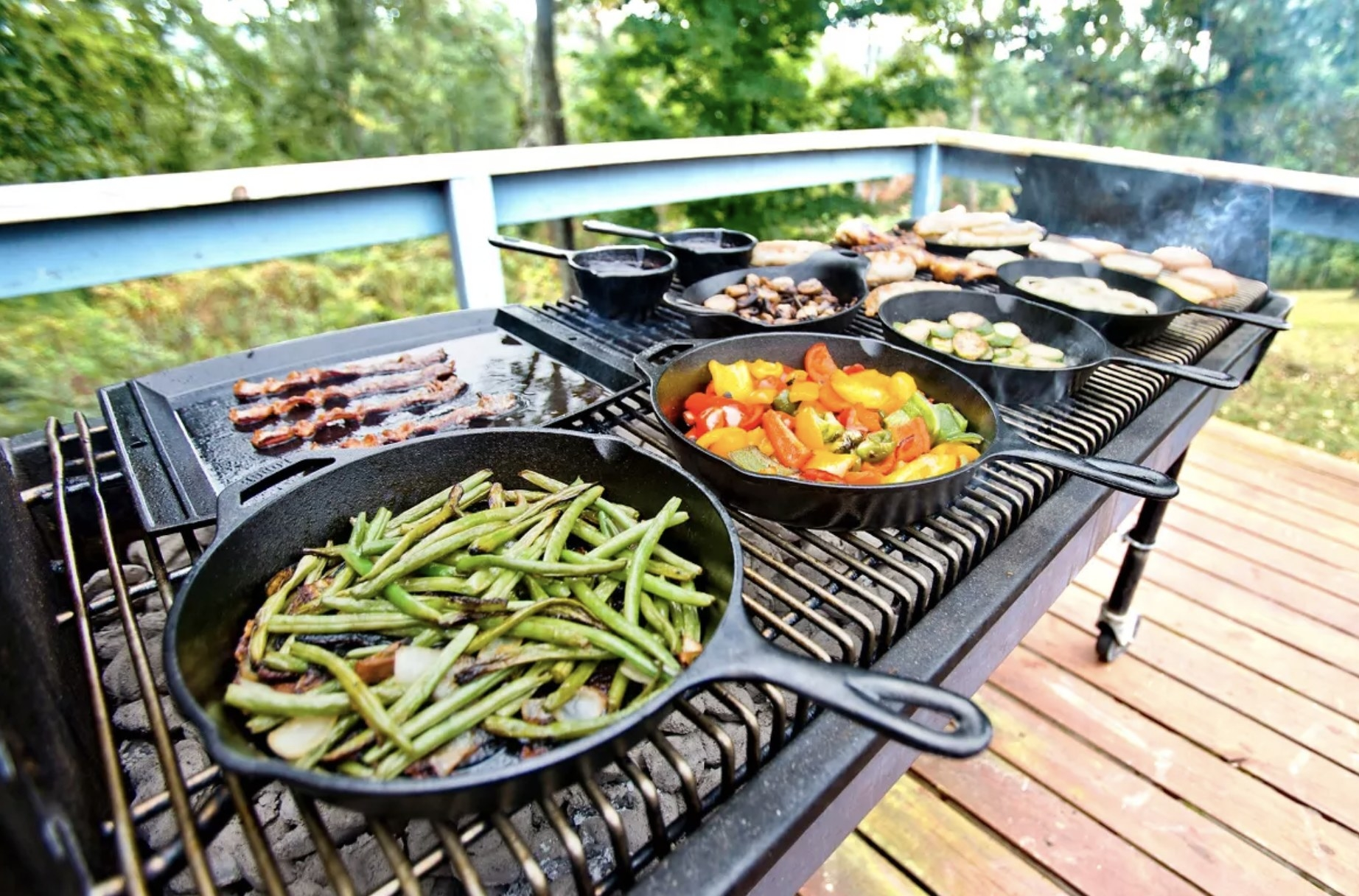 four cast iron skillets on a grill cooking vegetables