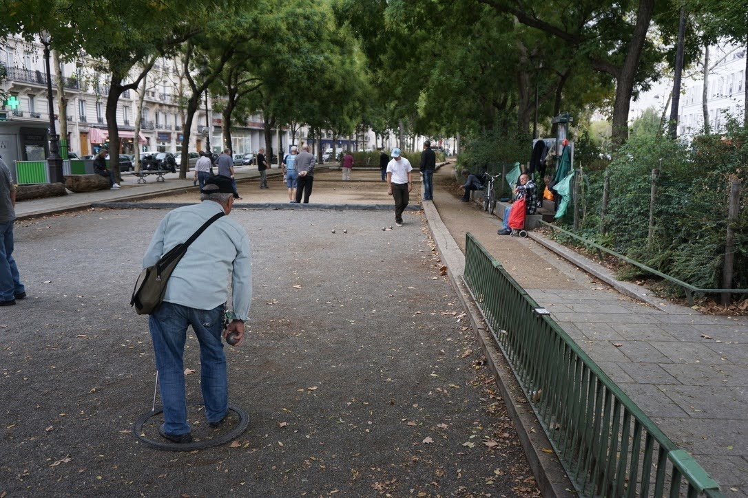 People playing pétanque on a gravel court in Paris