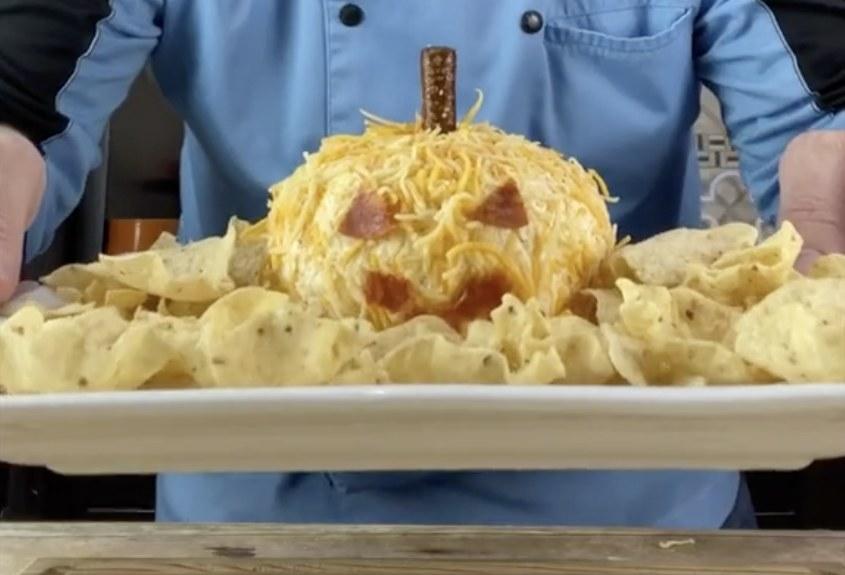 A cheese dip that is shaped like a pumpkin