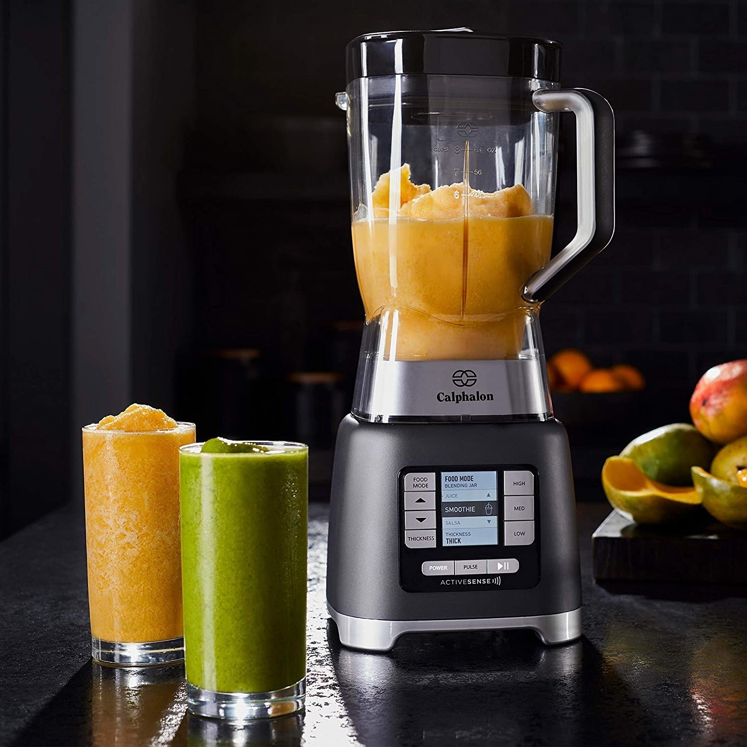 A blender filled with a smoothie with two glasses of smoothie next to it