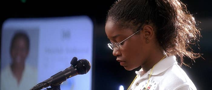 A young girl stands at a microphone
