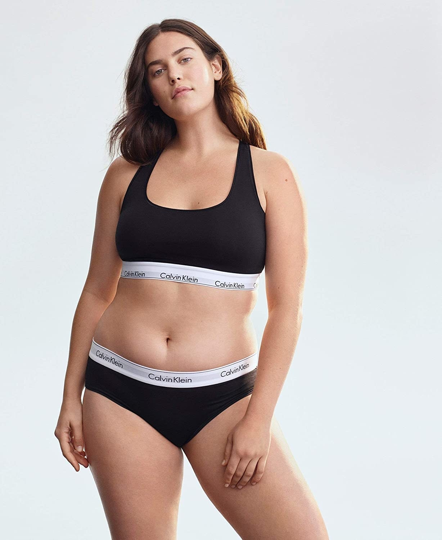 A model wearing the black bralette and undies, which both have white Calvin Klein logo trim
