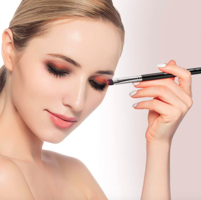 Model holds black angled makeup brush to apply eyeshadow to their eyes