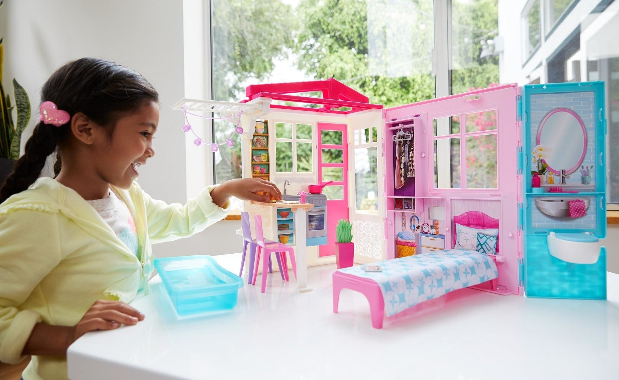Child playing with the large pink house setup