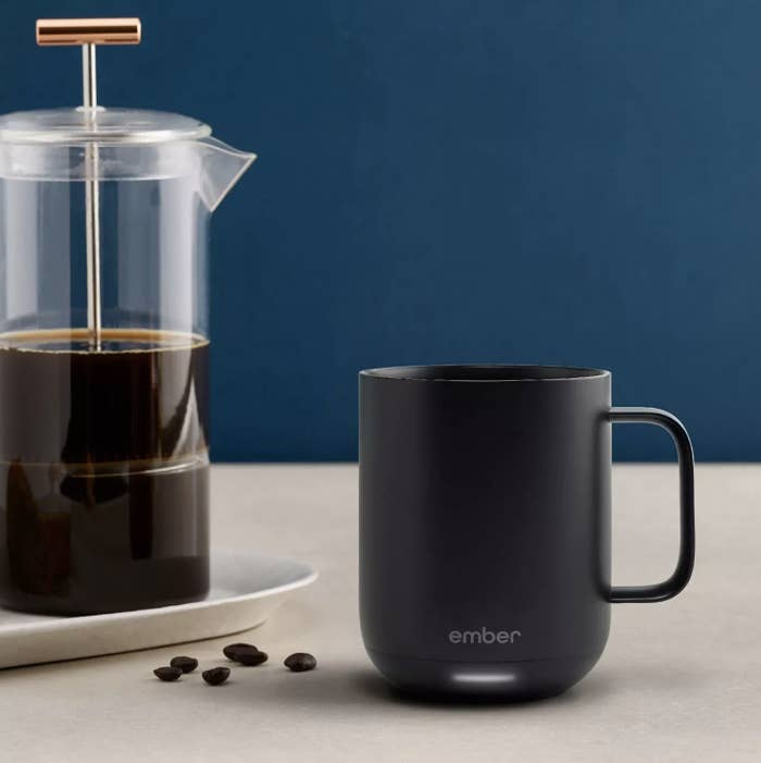 a black ember mug with an LED light at its base sitting next to a french press
