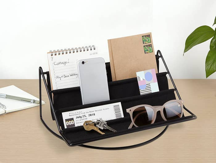 The felted hammock on a desk containing sunglasses, a phone, mail, and some keys