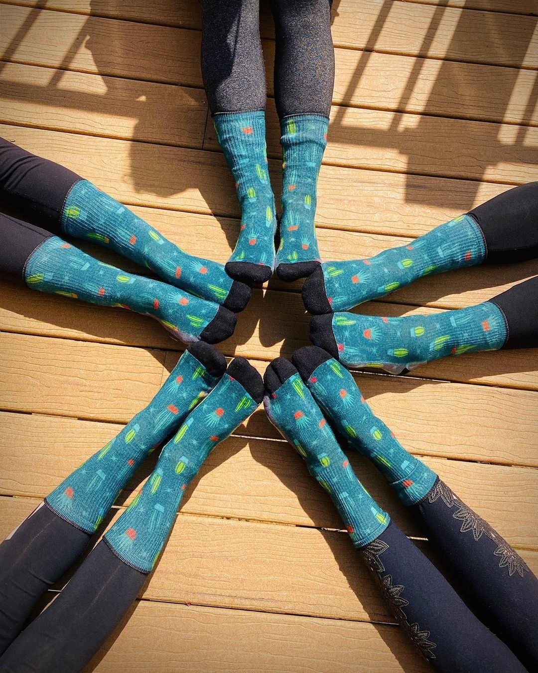 Several pairs of feet wearing the teal socks
