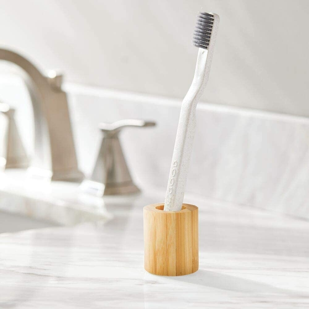 A close up of a toothbrush placed in the bamboo holder