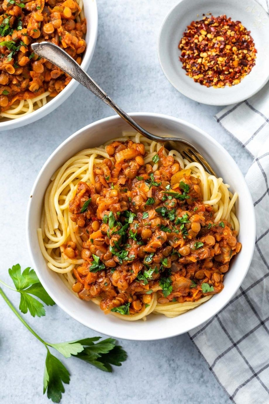 A bowl of spaghetti with lentil Bolognese and fresh parsley.