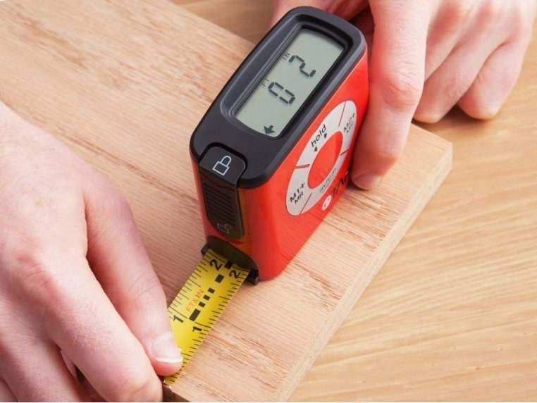 The thin square tape measure with digital reading on top being used to measure a piece of wood