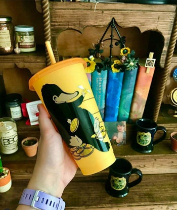 a yellow tumbler with an illustration of a niffler on it