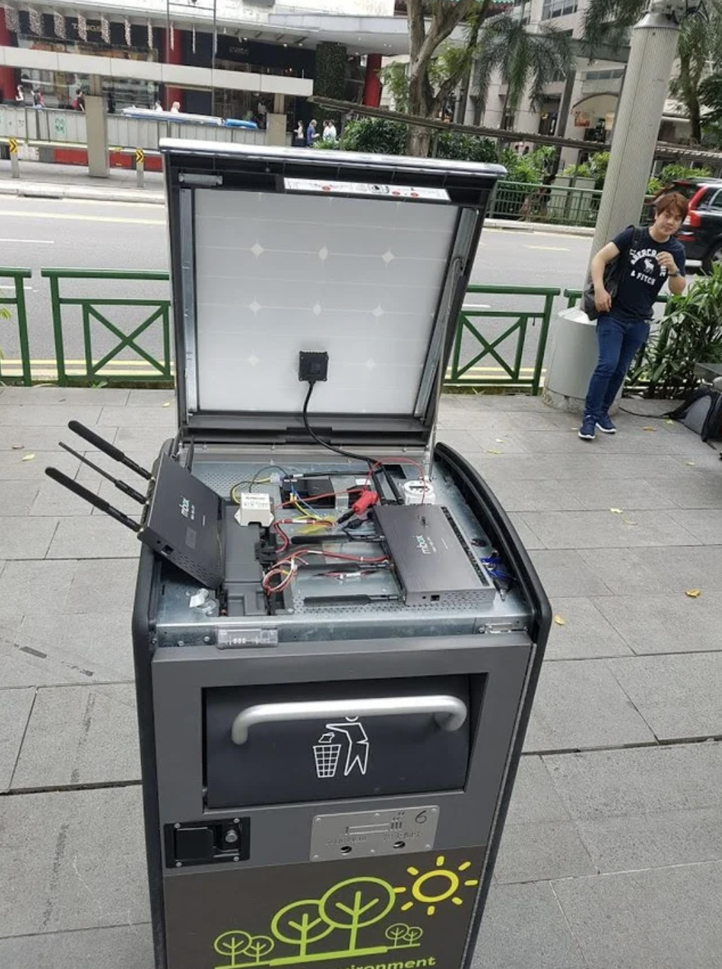 A public trash bin with modems, routers, and cords set up on top