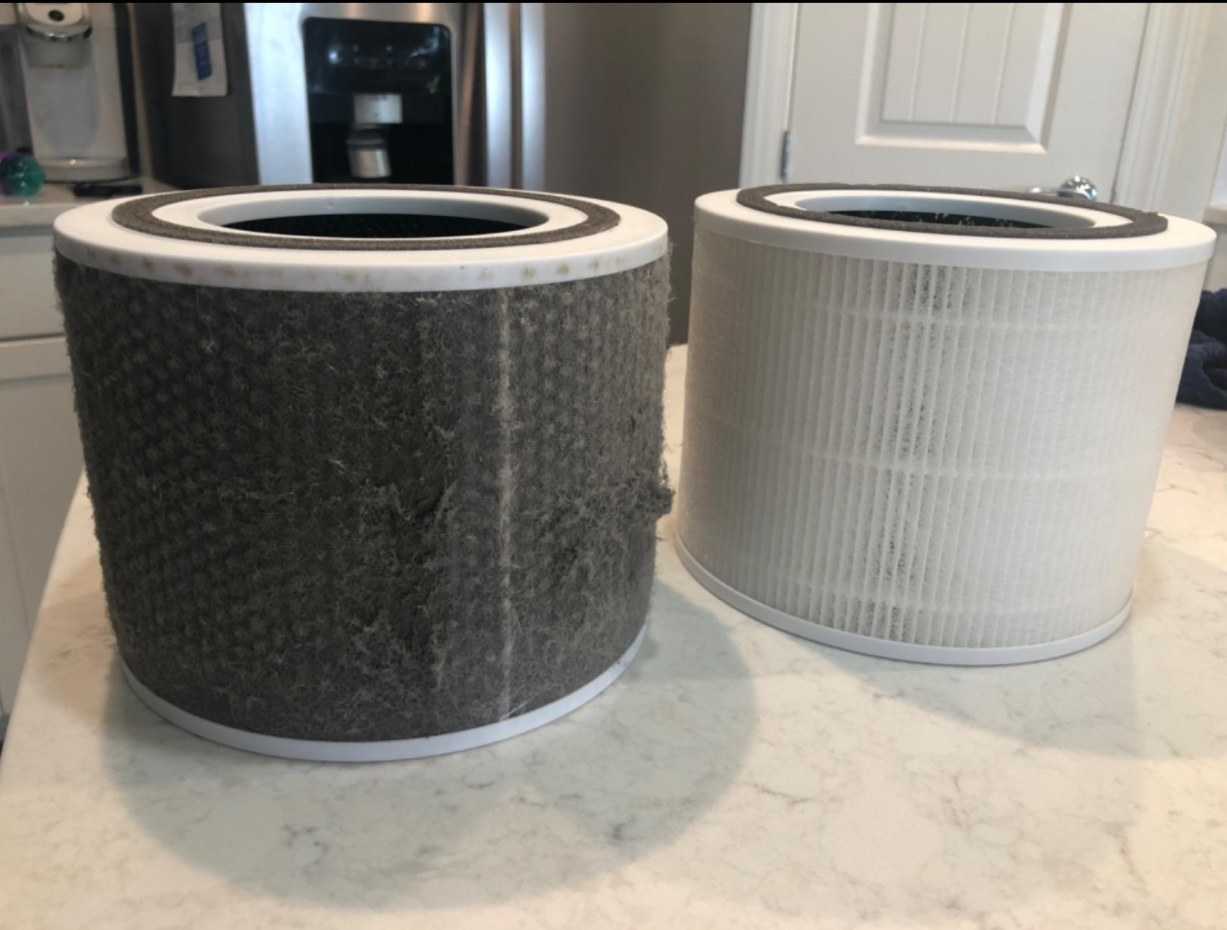 A clean filter from the air purifier beside a dirty filter that picked up dirt and pet dander