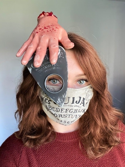 A woman in a Ouija board mask with a planchette over her eye and a fake hand attached to it