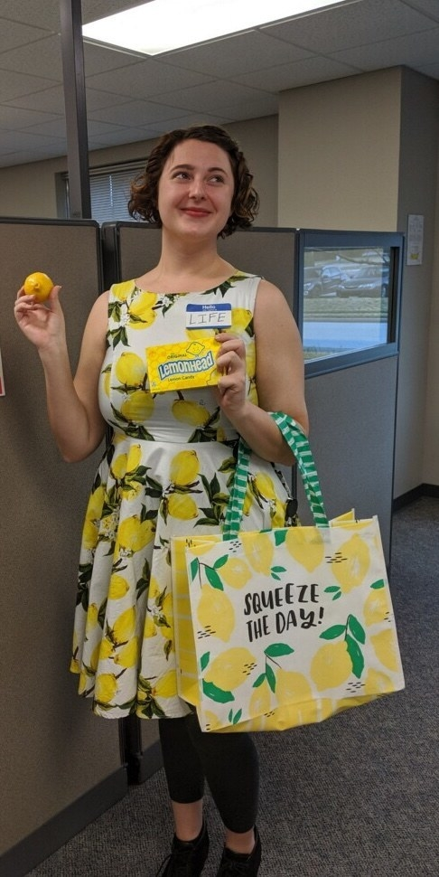 """A woman in a lemon dress and a name tag reading """"hello, my name is life"""" who is handing out lemons and lemonhead candy"""