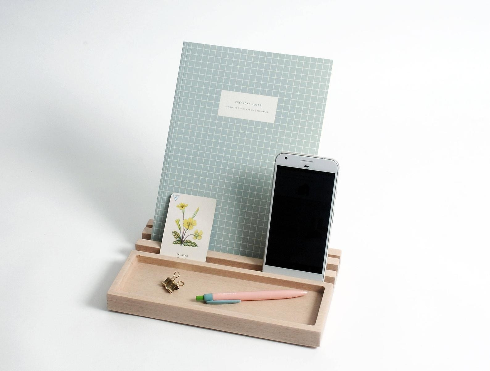 The rectangle-shaped light wood tray with slots that are holding a notebook and phone