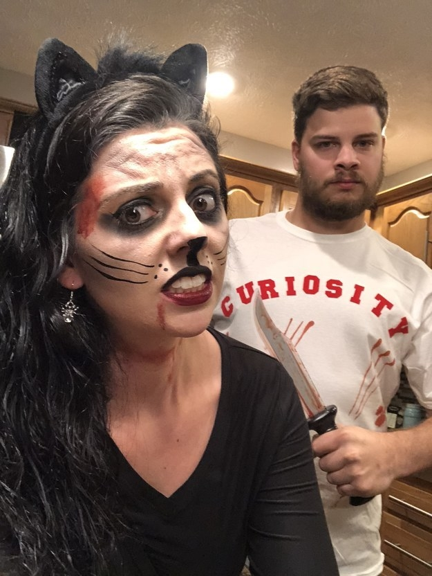 """A woman dressed as a bloody cat and a man with a knife wearing a shirt that says """"curiosity"""""""