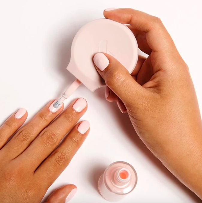 Model holds Olive & June The Poppy Manicure Tool while painting nails with pink polish