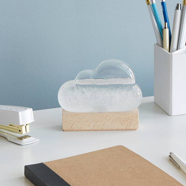 The clear cloud-shaped device with wood base