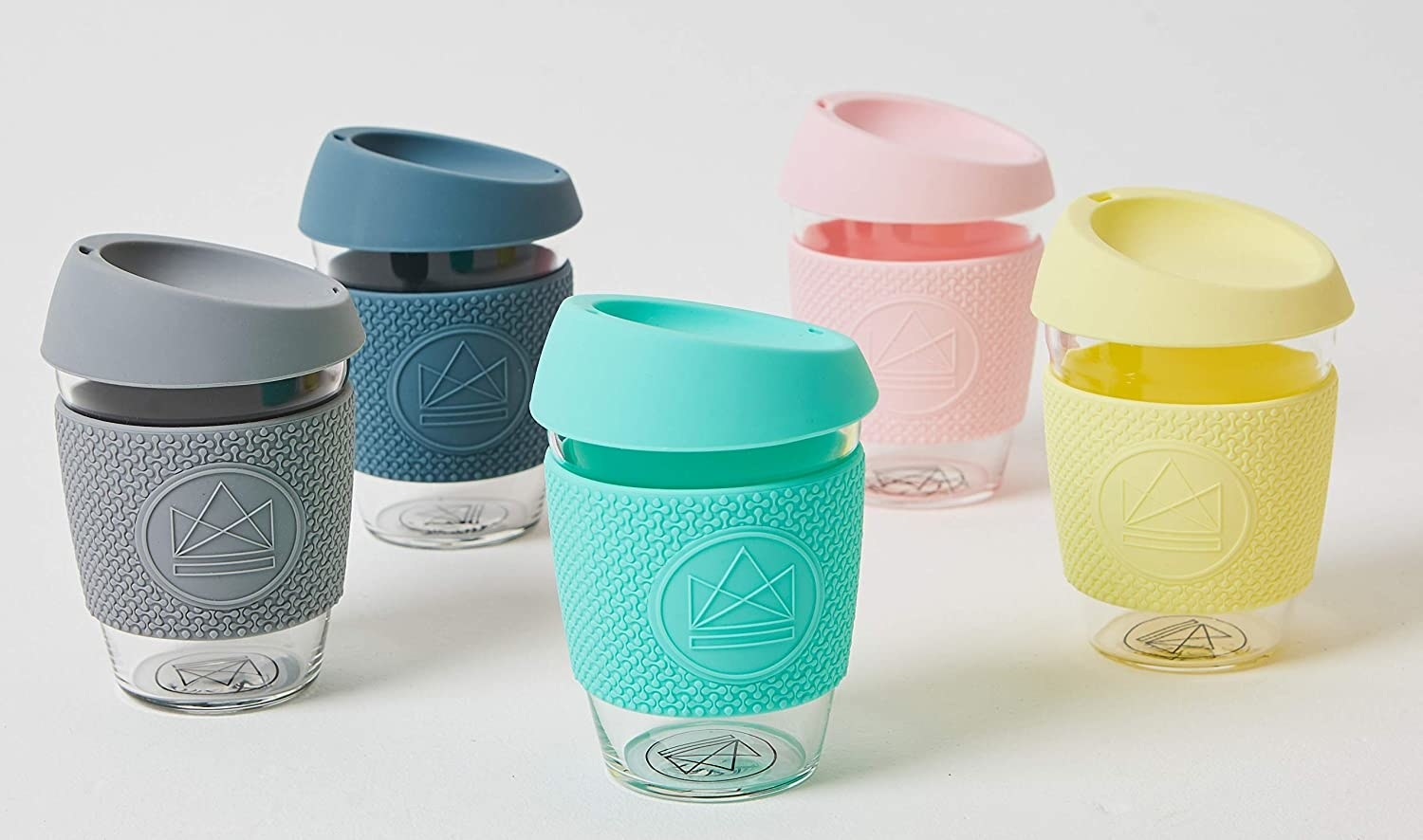 Five small glass coffee cups with silicone lids and sleeves on them