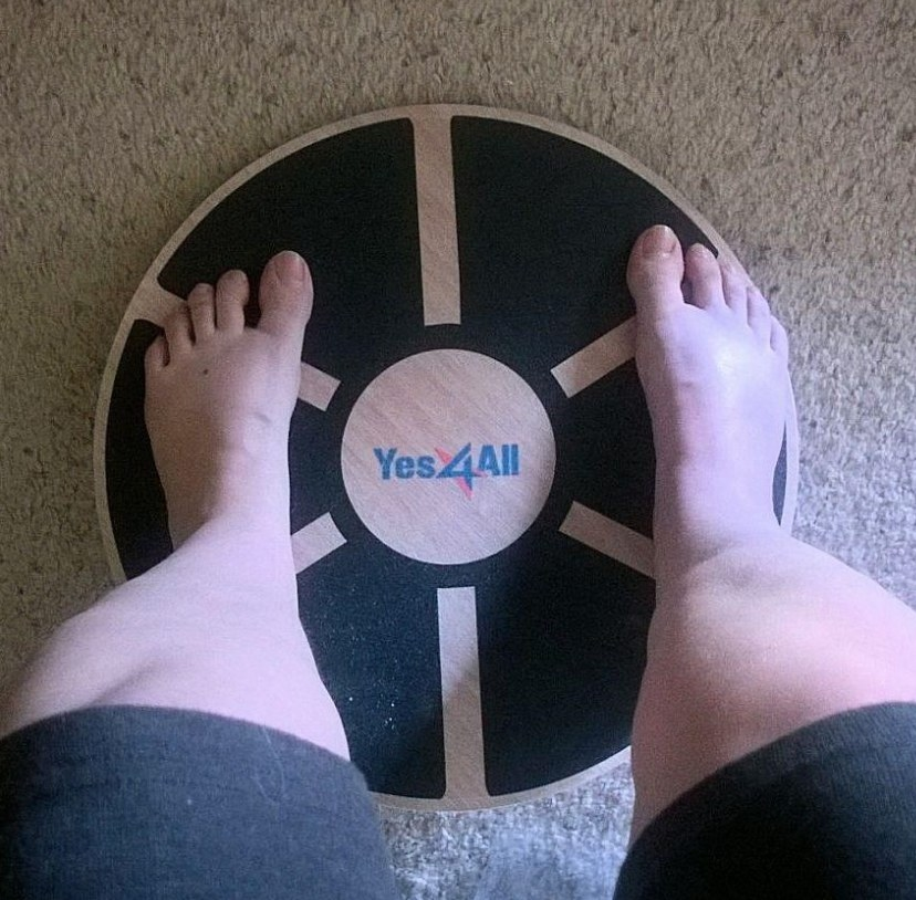 A person's legs standing on a stability board