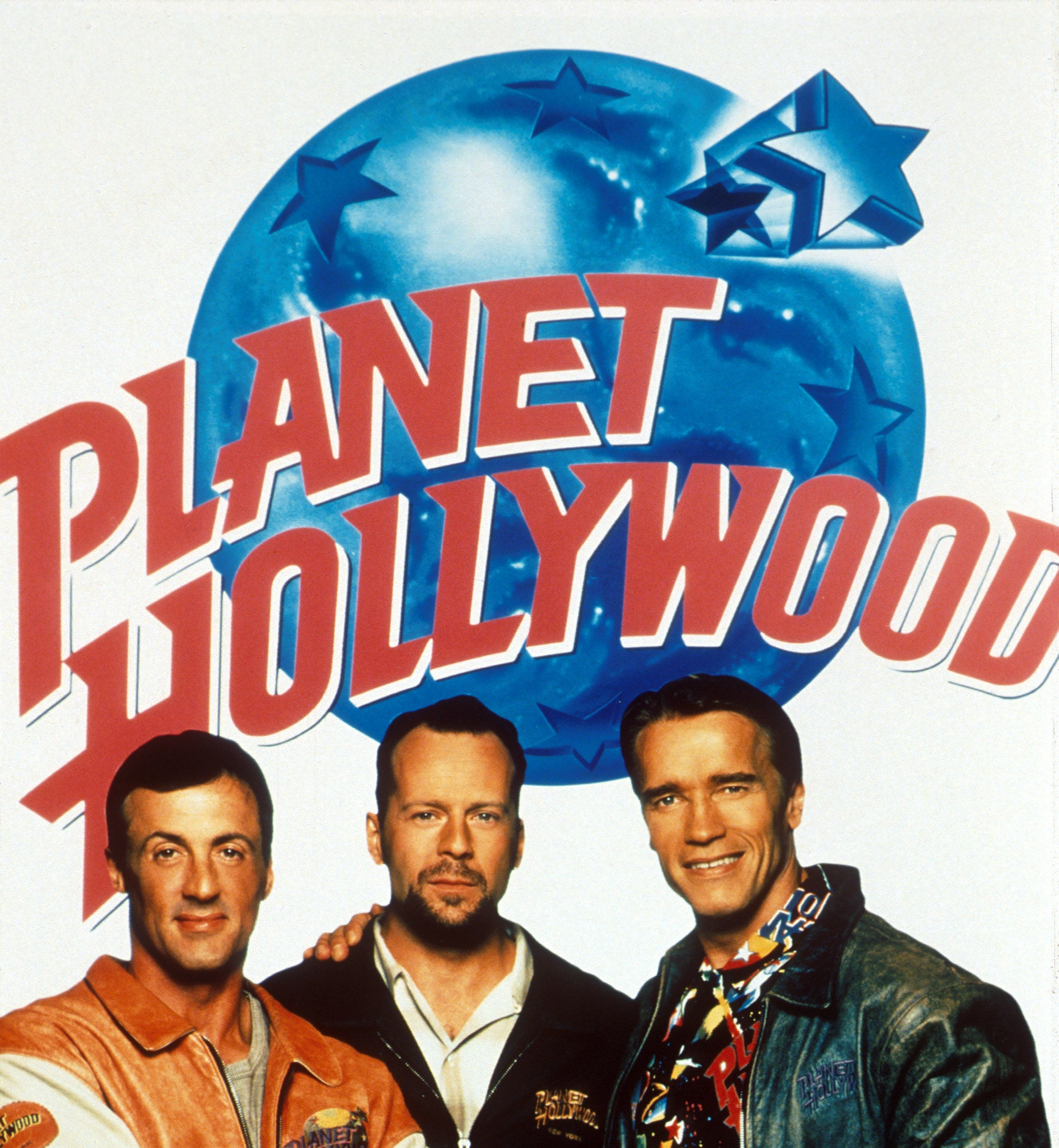 A poster for Planet Hollywood featuring Sylvester Stallone, Bruce Willis, and Arnold Schwarzenegger
