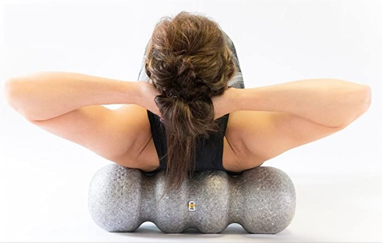 A woman using a foam roller with grooves